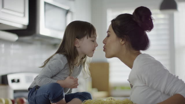 medium shot of daughter and mother kissing in kitchen / provo, utah, united states - mother and daughter stock videos and b-roll footage