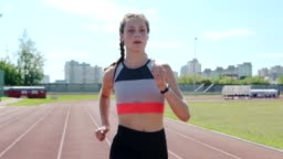 Medium shot of determined teenage female athlete with two braids running on track in slow motion