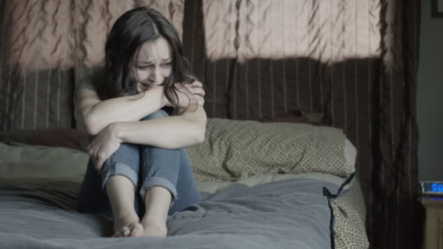 vidéos et rushes de medium shot of domestic abuse victim crying on bed / springville, utah, united states - springville utah