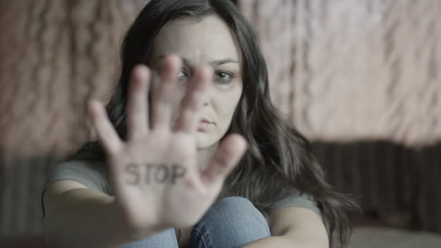 Medium shot of domestic abuse victim showing stop on palm of hand / Springville, Utah, United States