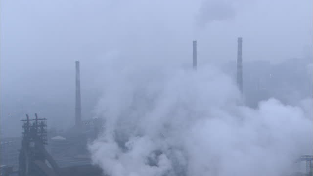 medium shot of factory enveloped in smoke - luftverschmutzung stock-videos und b-roll-filmmaterial