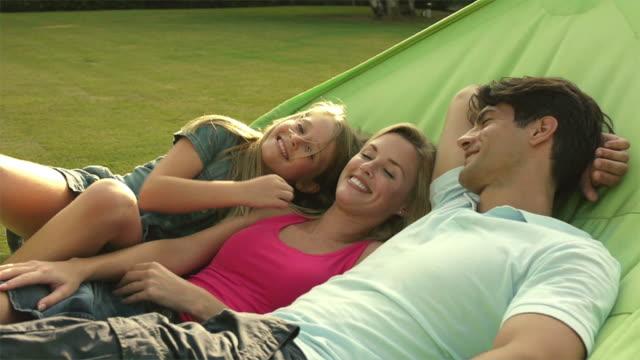 vídeos de stock e filmes b-roll de medium shot of family in hammock/sotogrande,spain - fotografia de três quartos