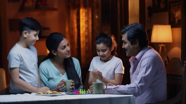 medium shot of family playing ludo board game during tea time while sitting at table at home - leisure games stock videos & royalty-free footage