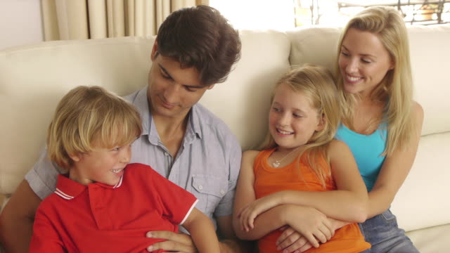 medium shot of family sitting on couch together/sotogrande,spain - four people stock videos & royalty-free footage