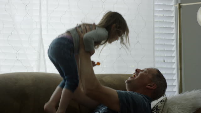 Medium shot of father and daughter playing on sofa / Provo, Utah, United States