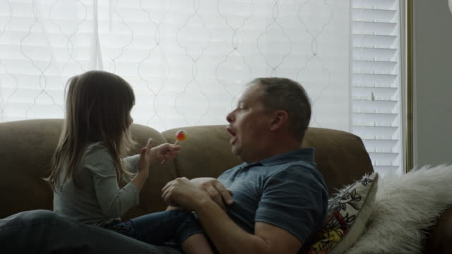 medium shot of father and daughter playing with lollipop / provo, utah, united states - provo stock videos & royalty-free footage