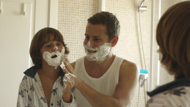 Medium shot of father and son with shaving cream on their faces/Marbella region, Spain