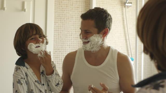 medium shot of father and son with shaving cream on their faces/marbella region, spain - お手洗い点の映像素材/bロール