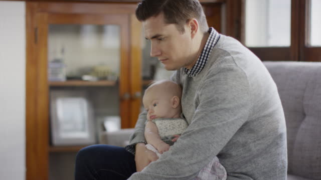 stockvideo's en b-roll-footage met medium shot of father holding baby daughter and typing on laptop / provo, utah, united states - provo