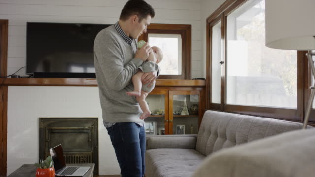 stockvideo's en b-roll-footage met medium shot of father walking while feeding bottle to baby daughter / provo, utah, united states - zuigfles