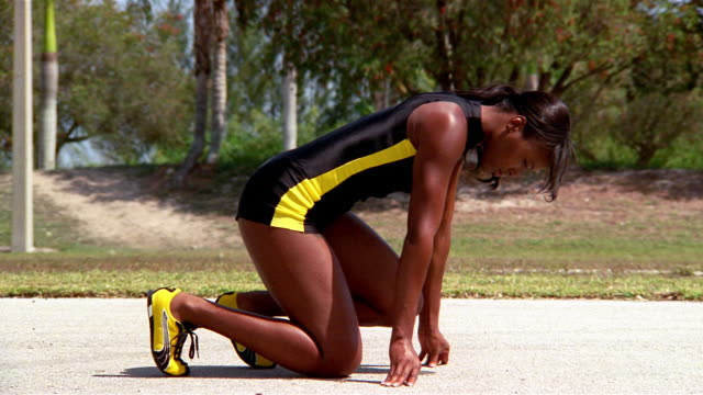 medium shot of female track runner in starting position / motorcycle pulling up beside her - spandex stock videos & royalty-free footage