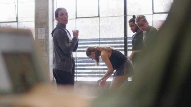 stockvideo's en b-roll-footage met medium shot of female trainer talking and dance troupe rehearsing - publiciteitsmedewerker