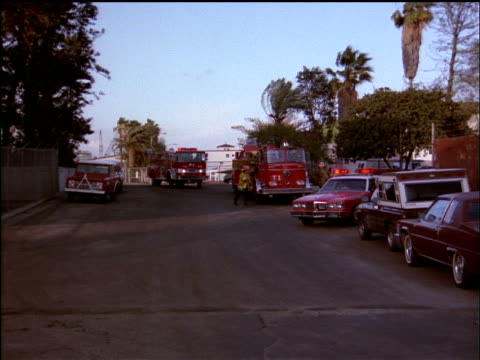 medium shot of fire trucks and chief's car arriving at a fire. - 1分以上点の映像素材/bロール