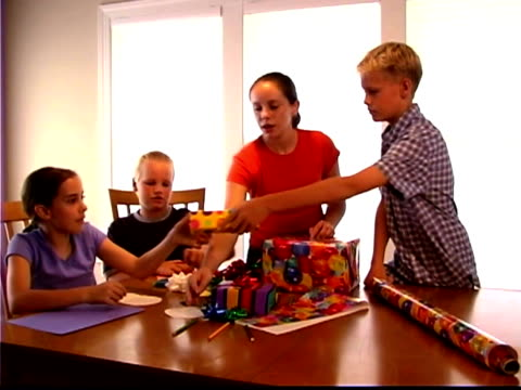 medium shot of four kids around a table, wrapping presents and making cards. - bald head island stock videos & royalty-free footage