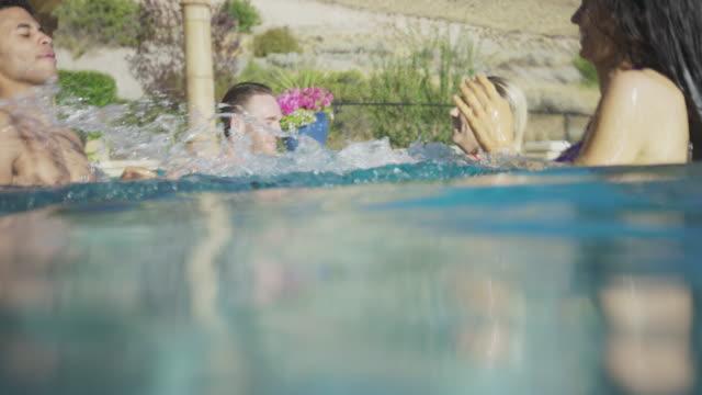 vídeos de stock e filmes b-roll de medium shot of friends splashing in swimming pool / cedar hills, utah, united states - cabelo molhado