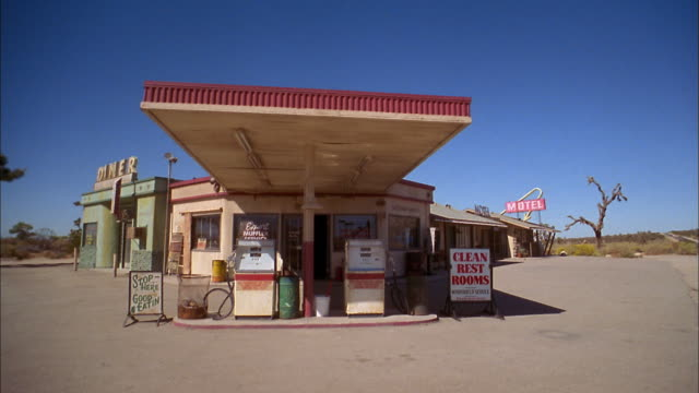 medium shot of gas station w/gas pumps in the foreground - fuel pump stock videos and b-roll footage