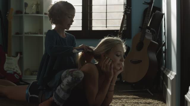 medium shot of girl brushing teenage sisters hair in bedroom / sandy, utah, united states - lying on front stock videos & royalty-free footage