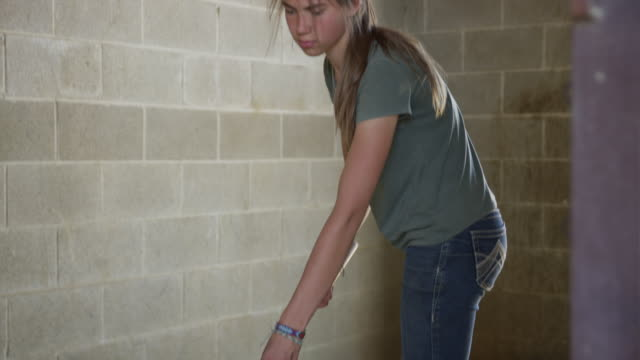 medium shot of girl cleaning floor of stable / lehi, utah, united states - lehi stock videos & royalty-free footage