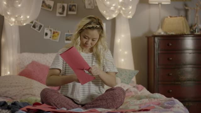 medium shot of girl cutting paper hearts in bedroom / cedar hills, utah, united states - one teenage girl only stock videos & royalty-free footage