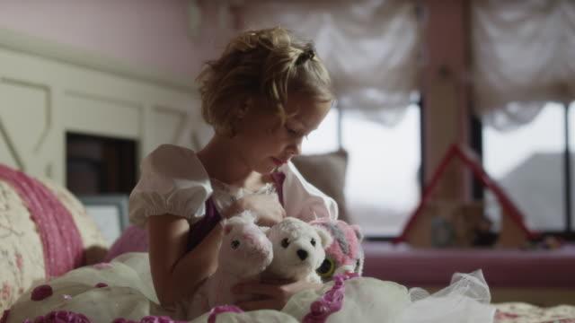 vídeos de stock, filmes e b-roll de medium shot of girl hugging and petting stuffed animals on bed / sandy, utah, united states - animal de brinquedo