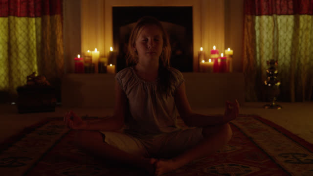 Medium shot of girl meditating in lotus position with candles in background / Cedar Hills, Utah, United States