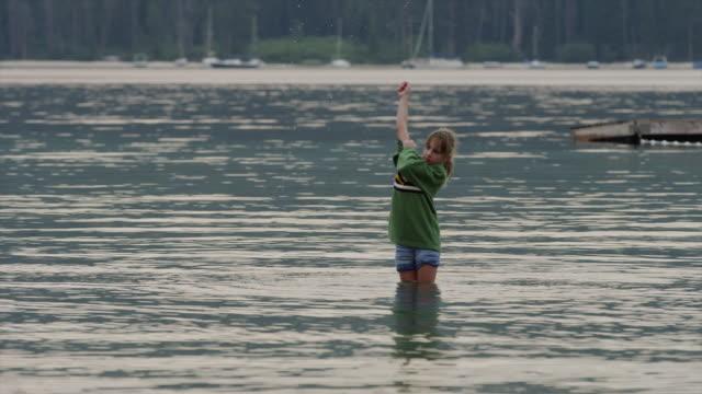 vídeos y material grabado en eventos de stock de medium shot of girl playing in lake / redfish lake, idaho, united states - cabello recogido