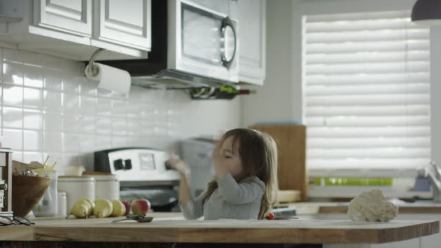medium shot of girl playing with flour in kitchen / provo, utah, united states - unordentlich stock-videos und b-roll-filmmaterial