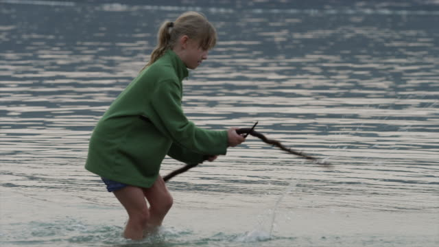 Medium shot of girl playing with stick in lake / Redfish Lake, Idaho, United States