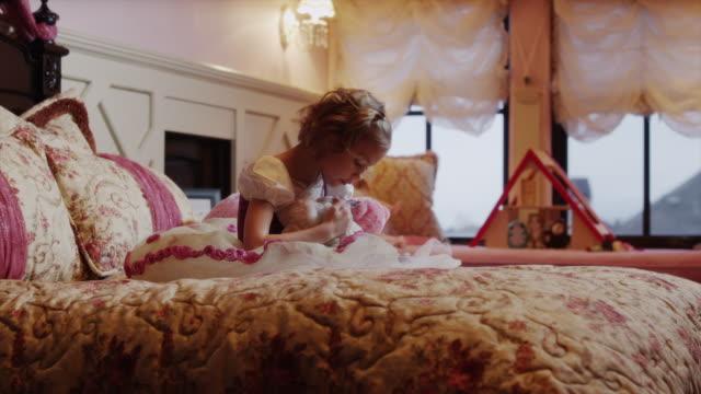 vídeos de stock, filmes e b-roll de medium shot of girl playing with stuffed animals on bed / sandy, utah, united states - animal de brinquedo
