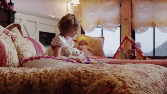 vídeos de stock, filmes e b-roll de medium shot of girl reading book to stuffed animals on bed / sandy, utah, united states - animal de brinquedo