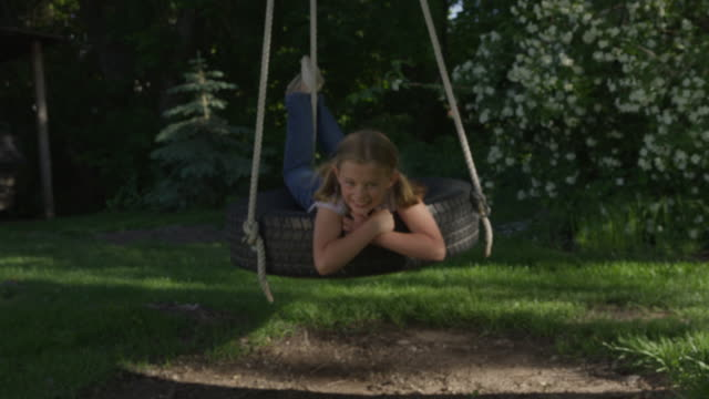 medium shot of girl smiling on tire swing / springville, utah, united states - springville utah stock-videos und b-roll-filmmaterial