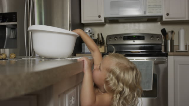 medium shot of girl taking cookie dough from bowl in kitchen / orem, utah, united states - unfug stock-videos und b-roll-filmmaterial