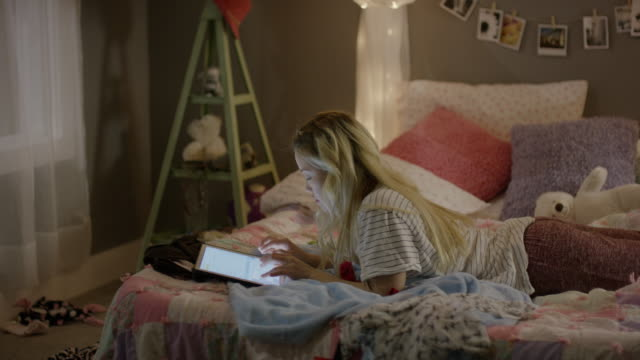 Medium shot of girl using digital tablet in bedroom / Cedar Hills, Utah, United States