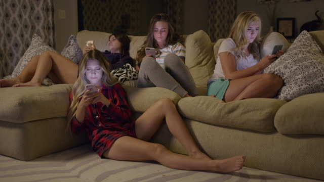 Medium shot of girls distracted by cell phones at slumber party / Cedar Hills, Utah, United States