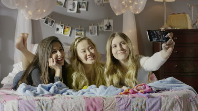 medium shot of girls taking selfie in bedroom / cedar hills, utah, united states - photographing stock videos and b-roll footage