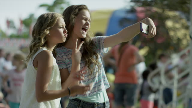 Medium shot of girls taking self-portrait with cell phone / Pleasant Grove, Utah, United States