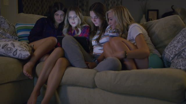 medium shot of girls watching digital tablet at slumber party / cedar hills, utah, united states - only young women stock videos & royalty-free footage