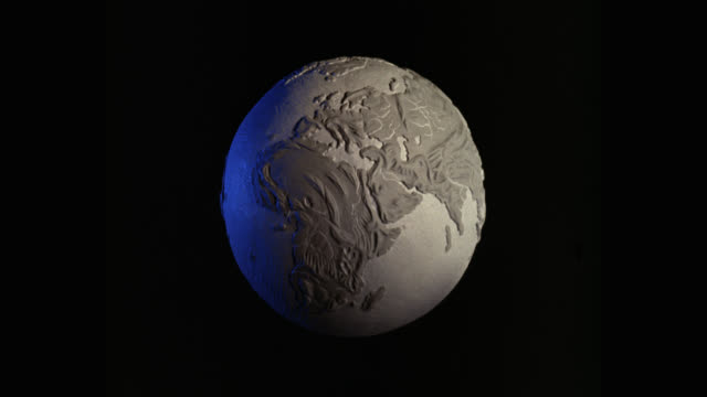 medium shot of globe spinning against black background - spinning stock videos & royalty-free footage