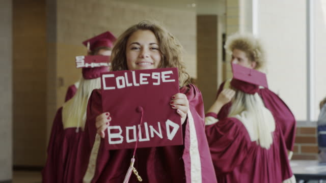 medium shot of graduate showing mortarboard with message in corridor / mapleton, utah, united states - mortar board stock videos & royalty-free footage