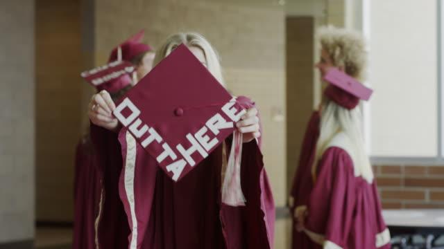 medium shot of graduate waving mortarboard with message in corridor / mapleton, utah, united states - mortar board stock videos & royalty-free footage