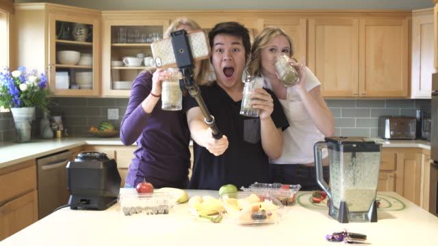 Medium shot of group of friends taking selfie while drinking juice