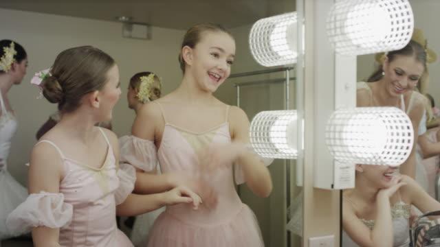 Medium shot of happy ballerinas stretching in dressing room mirror / Salt Lake City, Utah, United States