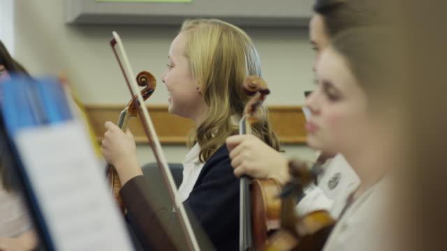 Medium shot of happy teenage girls waiting for orchestra practice / American Fork, Utah, United States