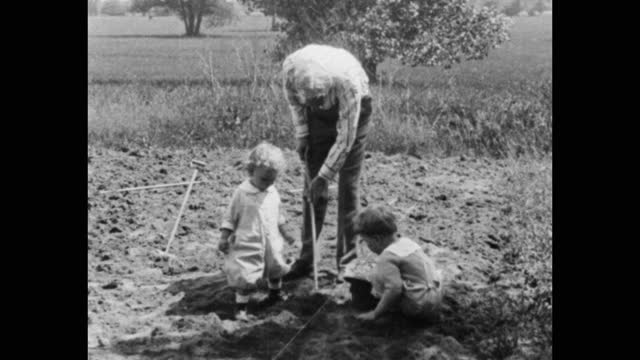 medium shot of henry ford digging in field with children, michigan, usa - three people stock videos & royalty-free footage