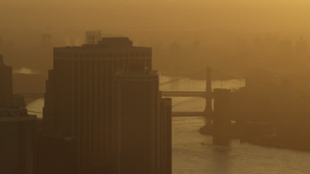 Medium shot of high-rise buildings with the Brooklyn Bridge and the Manhattan Bridge in the background at golden hour