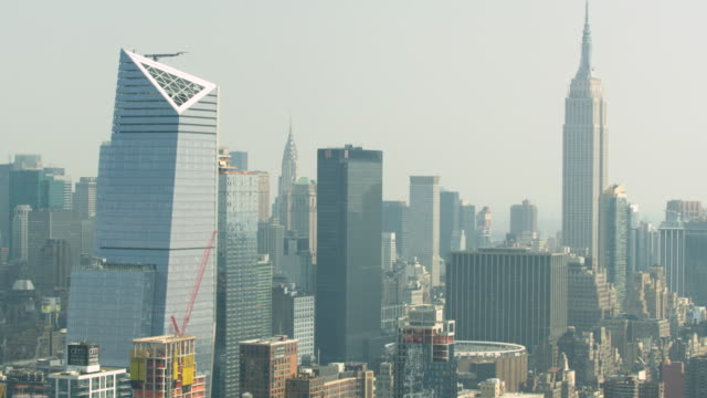 Medium shot of high-rise buildings with the Empire State Building in the background