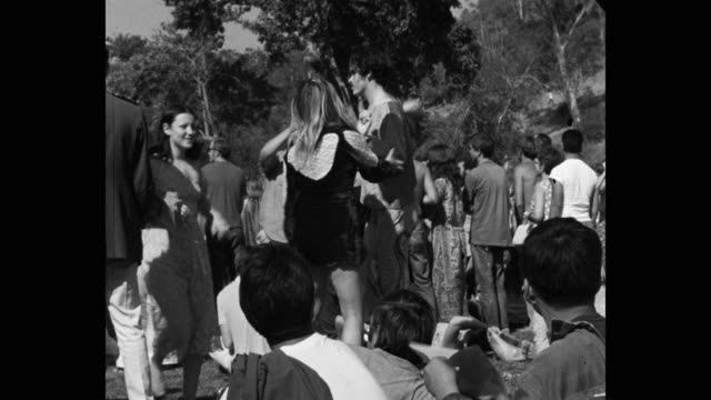 medium shot of hippie men and women dancing in public park - hippy stock videos & royalty-free footage