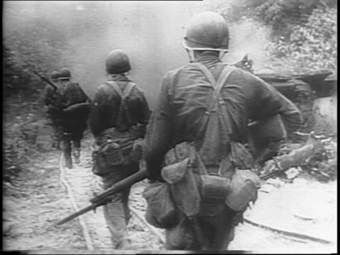 vidéos et rushes de medium shot of infantry carrying a wounded man with his rifle / medium shots of troops and tanks moving along a trail / soldiers finding cover in the... - infanterie