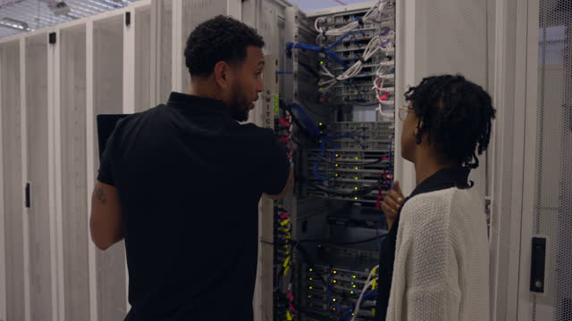 medium shot of it professionals in discussion while working on server rack in data center - scrutiny stock videos & royalty-free footage