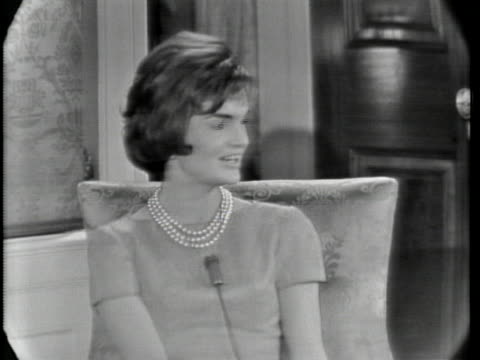 medium shot of jacqueline kennedy sitting on a chair. she has short hair and is wearing a dress and a pearl necklace. she has a microphone clipped to... - jackie kennedy stock videos & royalty-free footage